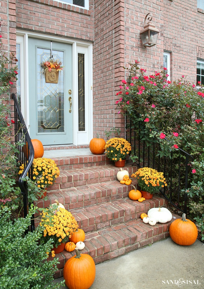 Decorating a front porch for fall in orange and white pumpkins