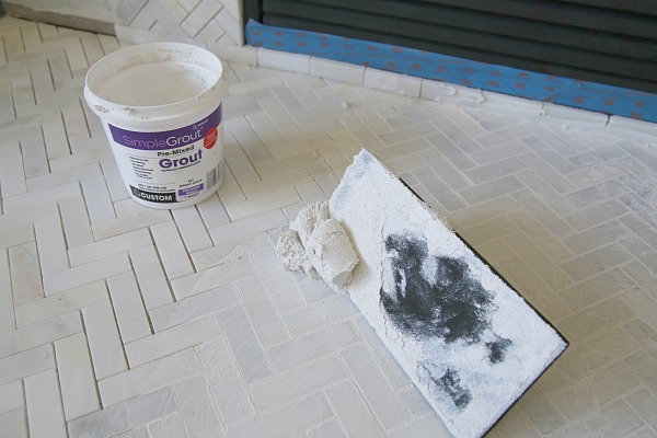 Applying grout to marble tile