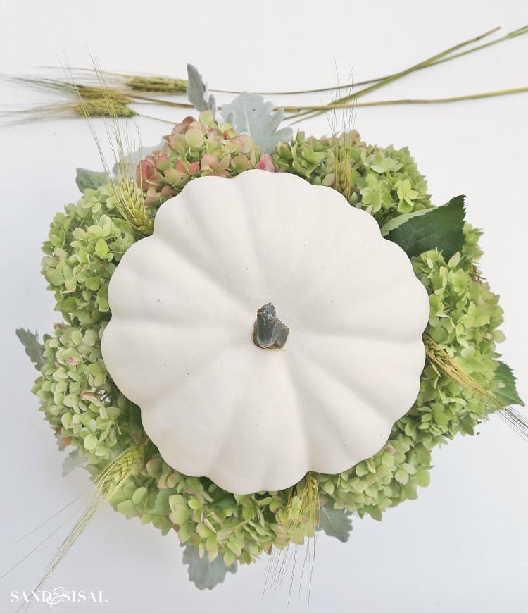 step-4-insert-wheat-straw-and-pumpkin. White Pumpkin and Hydrangea Fall Centerpiece