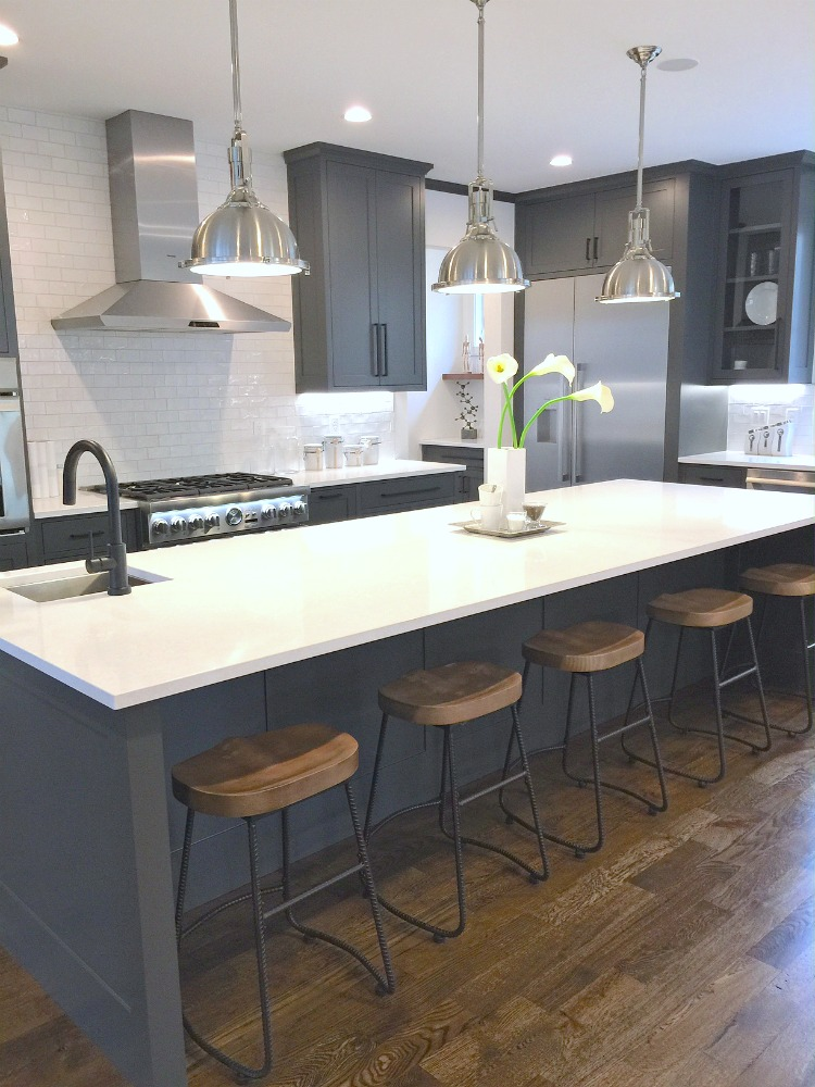 sustainable9-home-tour - Charcoal Gray Kitchen Cabinets with White Cambria Quartz Counters and Stainless Steel Pendants.