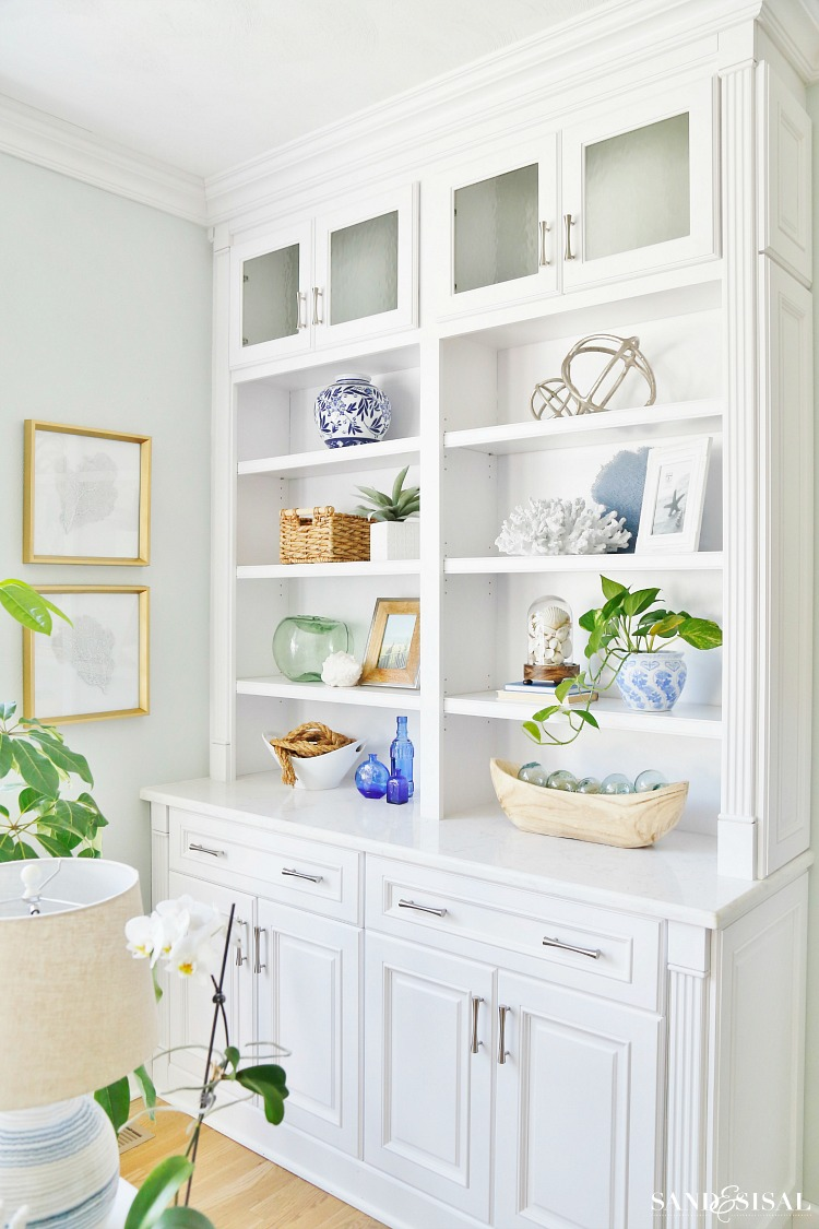 How to decorate bookcases -Escape to the sea with this summer blues coastal family room tour! Get easy coastal decorating ideas to transform your home into a chic coastal retreat. Complete with product source links!